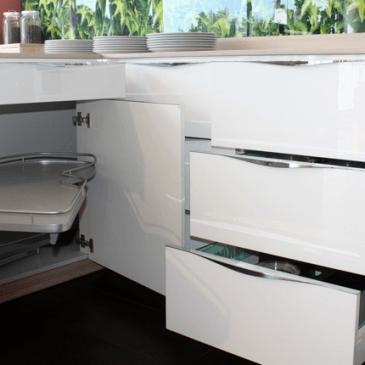 Primer moderne bele kuhinje s polotokom in veliko predali