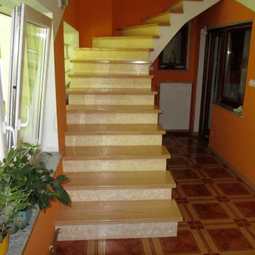 Lesene nastopne stopnice na zavitem betonskem stopnišču