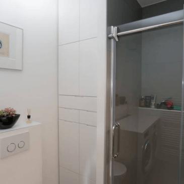 Visoka kopalniška omara, vgrajena med tuš kabino in zidno steno